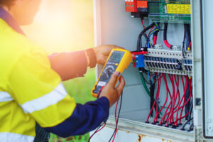 Workers use a Multimeter to measure the voltage of electrical wires produced from solar energy to confirm systems working normally.