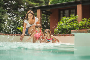 Mom and her twin daughters playing in the pool