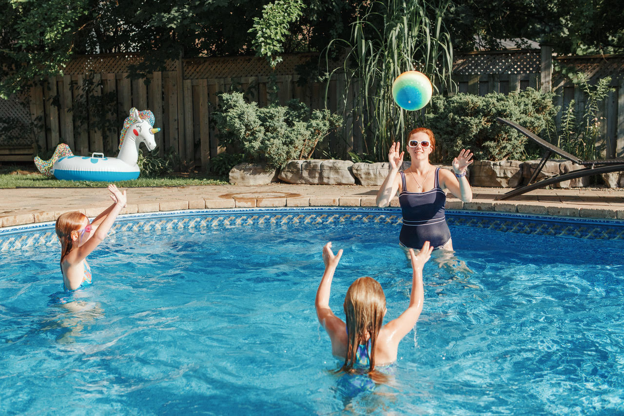 Mother playing ball with daughters children in swimming pool on home backyard. Mom and sisters siblings having fun in swimming pool together. Summer outdoor water activity for family and kids.